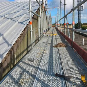 An independant gable scaffolding complete with a non-slip walkway not only complies with HSE recommendations but is safer than using cheaper edge protection as the old fragile roof becomes the walkway.